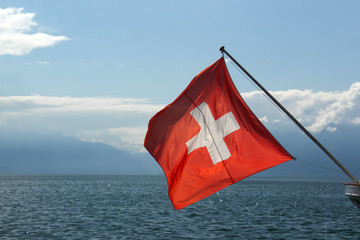 Beautiful Swiss flag attached to a ship, the sunlight creates a stunning effect in the flag. Location: Lake Geneva, Lausanne, Switzerland, summer 2019.