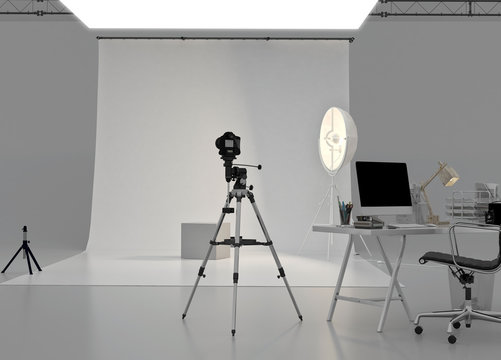 Empty modern photo studio interior with professional lighting equipment, soft box lights, reflectors, camera, tripods, computer, white backdrop