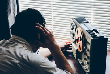 Special agent listens on the reel tape recorder. Officer wiretapping in headphones. KGB spying of conversations. - fototapety na wymiar
