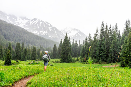 Open valley with man hiker walking in rain on Conundrum Creek Trail in Aspen, Colorado in 2019 summer on cloudy day and dirt road