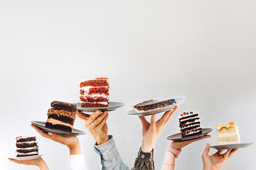Concept for cafe or bakery with desserts: plates with different cakes in people's hands, place for your text