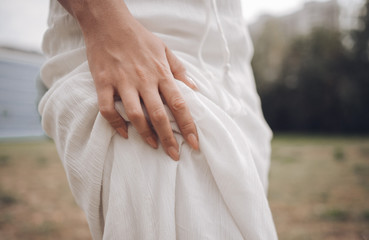female hand squeezes the white fabric of the dress