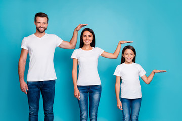 Portrait of charming family holding palm wearing white t-shirt denim jeans isolated over blue background