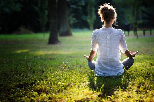 young woman practicing yoga and meditating in the forest