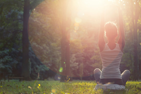 Woman meditating and practicing youga in the forest