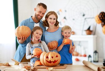 happy Halloween! family mother father and children cut pumpkin for holiday at home Wall mural