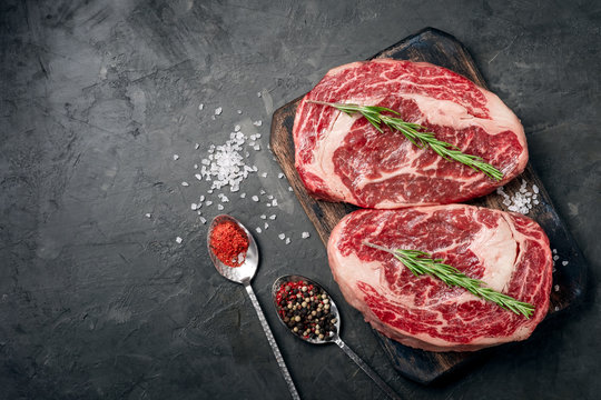 Two raw rib eye steak on the dark stone background prepared for cooking. Marbled beef top view
