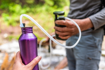 Man and woman couple using water filter on hiking trail river in Colorado to purify drinking water into bottle