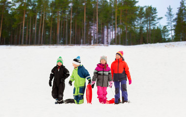 childhood, sledging and season concept - group of happy little kids with sleds in winter over forest background