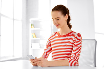 technology and people concept - smiling teenage girl with smartphone sitting at table