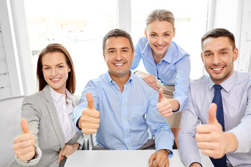 business people, gesture and success concept - happy smiling creative team showing thumbs up at office
