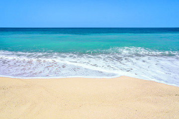 At a lonely sandy beach and turquoise sea