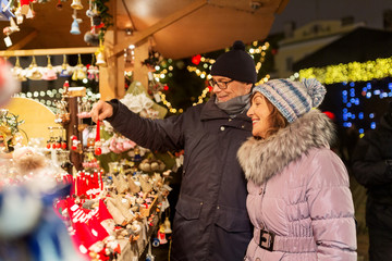 shopping, winter holidays and people concept - happy senior couple at christmas market souvenir...