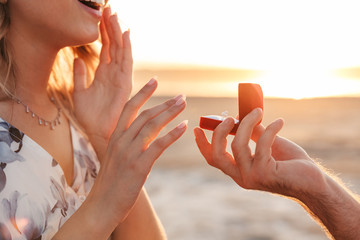 Cropped photo of romantic caucasian man making proposal to his girlfriend with ring walking on sunny beach