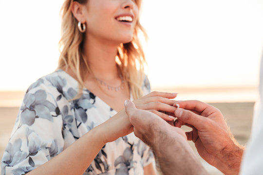 Cropped photo of young man putting engagement ring on woman's finger while walking on beach