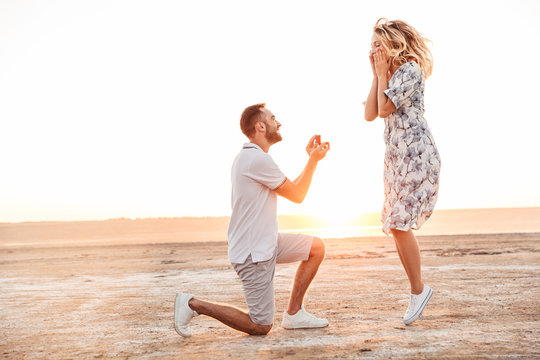 Photo of happy man making proposal to his excited woman with ring while walking on sunny beach