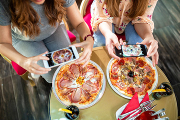 Two young girls taking a pic of their food