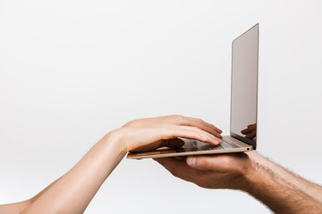 Man's and woman's hands isolated over white wall background holding laptop computer typing.