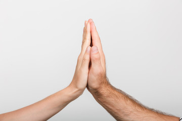 Man's and woman's hands give a high five to each other isolated over white wall background.
