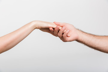 Gentleman holding woman's hand isolated over white wall background.