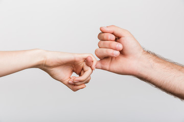 Man's and woman's hands holding little fingers of each other isolated over white wall background.