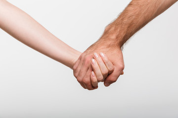 Man and woman holding hands of each other isolated over white wall background.