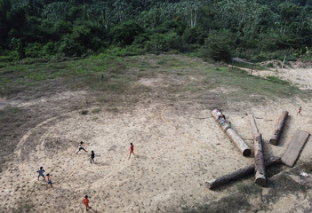 Children play next to logs that were illegally cut from Virola-Jatoba PDS in Anapu