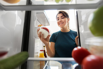healthy eating, food and diet concept - happy woman taking yoghurt from fridge at home kitchen