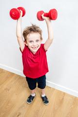 happy boy enjoying lifting up weights winning to express success