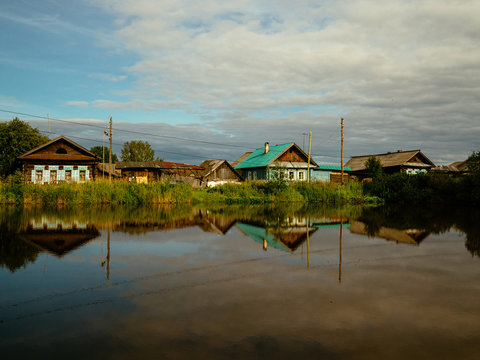 Houses in the village by the lake are reflected from the surface of the water