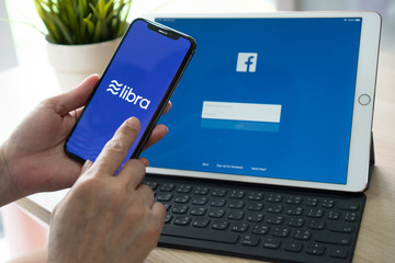 BANGKOK, THAILAND- June 26, 2019: Libra, Facebook's cryptocurrency, new internet cyber currency by FB social media for money business online digital technology, with logo on iPhone X and ipad pro