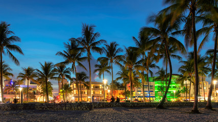 Nightlife in Miami Beach, Florida - palm trees, hotels and restaurants at sunset on Ocean Drive.
