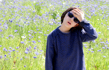 thinking child suffering from global pollution with spring floral meadow
