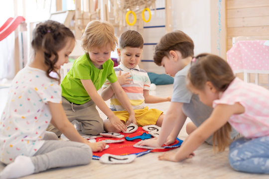 Children sit rounds on floor in kindergarten. Preschool kids learning how to tell time from clock and set the hands in the correct position. Real people, moments, authentic situations