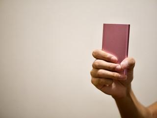 ピンクのモバイルバッテリーを持つ手