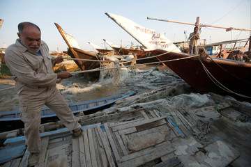 A man who repairs and sells fishing boats is seen on the bank of Shatt al-Arab in Al-Faw south of Basra