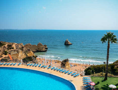Empty swimming pool overlooking Cova Redonda Beach in Algarve, Portugal during the summer - paradise holiday theme