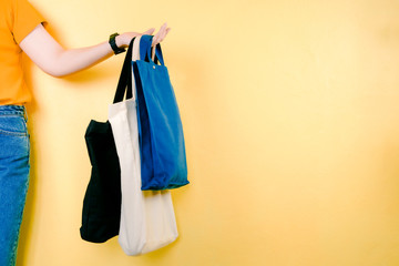save world and environment activity from beauty 30s to 40s asian woman shopping by use fabric bag instead of plastic bag with yellow pastel background