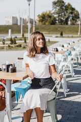 young woman in a white blouse and skirt sits on a summer terrace of a cafe in the city on a sunny morning. Stylish lifestyle