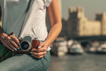 Woman holding retro vintage camera outdoors. Old camera. Female photography.