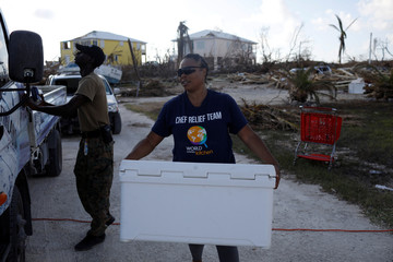 A volunteer of the NGO World Central Kitchen carries a cooler with food for distribution after Hurricane Dorian hit the Abaco Islands in Marsh Harbour