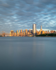 Manhattan bridge  Brooklyn Bridge and Financial District at sunrise with long exposure from East river