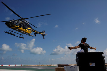 A volunteer of the NGO World Central Kitchen gestures as a helicopter leaves after delivering food for distribution, after Hurricane Dorian hit the Abaco Islands in Marsh Harbour