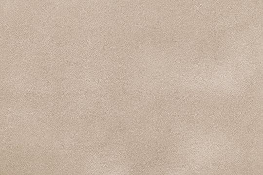 Light beige matte background of suede fabric, closeup.