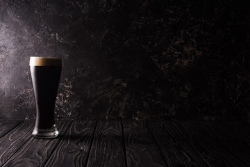 glass of dark beer on wooden table with shadow