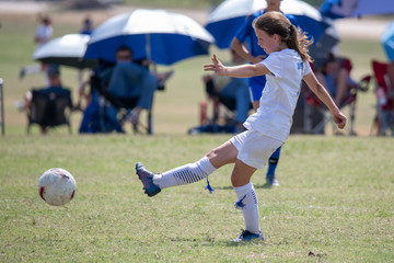 Young athletic teen girl playing in a soccer game