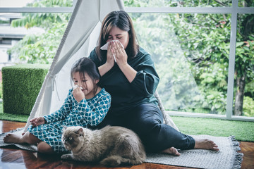 Asian mother and daughter, 6 years old, using tissue paper to wipe mucus Due to flu And allergic reactions to cat's fur, which are attached to clothing, to health care and family concept.