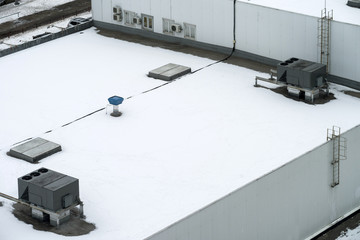 The external units of the commercial air conditioning and ventilation systems are installed on the roof of an industrial building. Winter photo.
