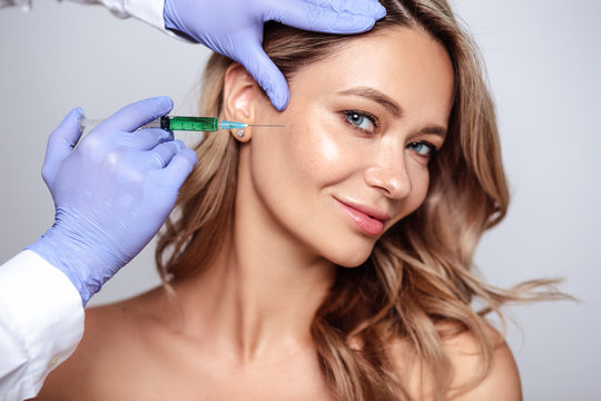 Close up portrait of blonde woman with cosmetologist hands near her face. Procedure in salon, spa and care