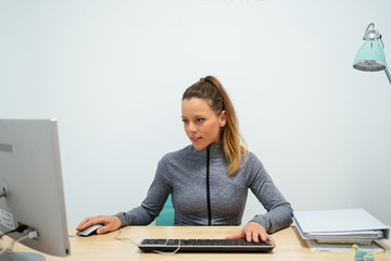 Charming girl dressed in a sweater and blond hair, works on her computer, in her office, a white...